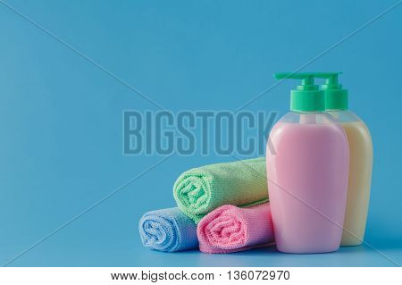 Colorful Towels And Liquid Soap Over Blue Background
