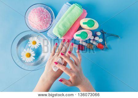 beautiful woman hands with cream  on blue