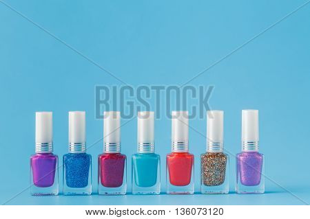 Few colored nail Polish on blue background