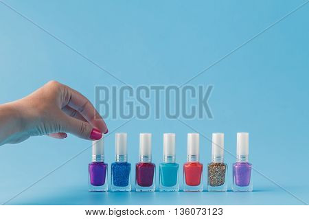 Female hand with stylish colorful nails on blue