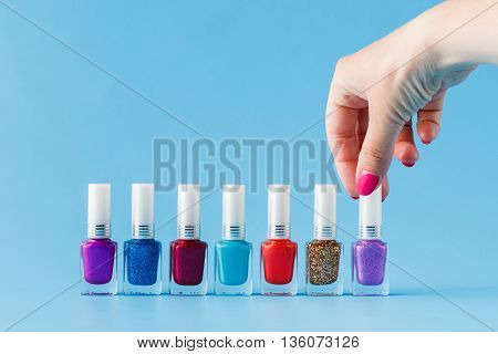 Group of bright nail polishes and woman's hand