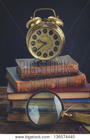 pile of old books with alarm clock, retro toned