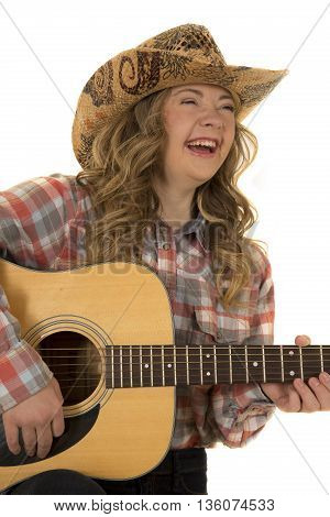 a close up of a cowgirl who has down syndrome playing her guitar laughing.