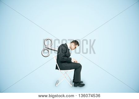 Businessman with a wind-up key on his back sitting on chair and using laptop on blue background. Concept of control