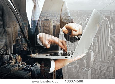 Concept of teamwork with businesspeople discussing project on laptop. New York city background. Double exposure