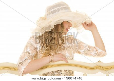 a woman with down syndrome touching her brim of her vintage hat looking to the side.
