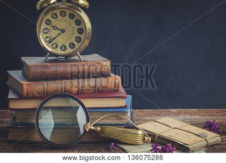 pile of old books with vintage alarm clock an looking glass, retro toned