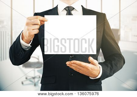 Businessman in suit holding blank paper sheet in office interior. Mock up