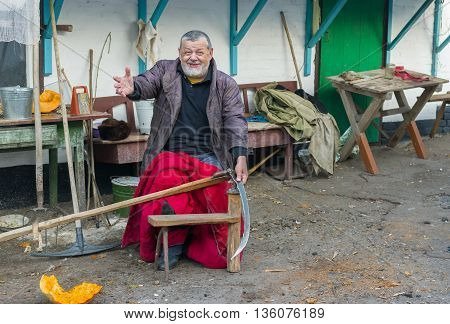 Cheerful Ukrainian peasant getting ready to whet a scythe at the homestead