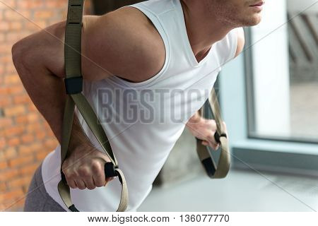 Motivated young sportsman is doing push-ups in gym. He is standing and leaning hands on trx equipment