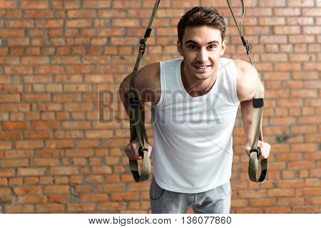 Attractive fit man doing push-ups with trx straps in gym. He is looking at camera and smiling