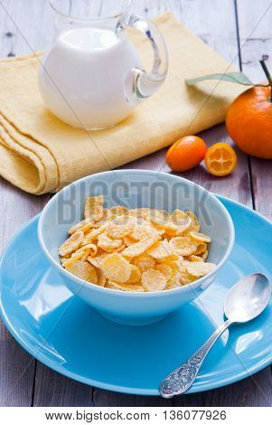 Healthy breakfast with corn flakes in a blue bowl