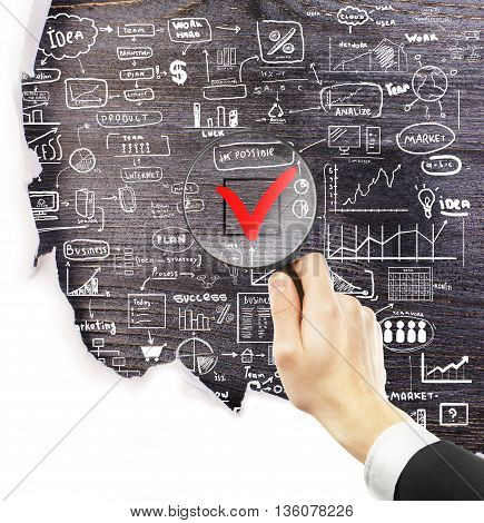 Businessman hand holding magnifier over red checkmark with business drawings around on dark wooden background under torn paper. Nothing is impossible concept