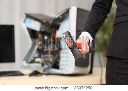 Computer absolutely destroyed by a hot-tempered businesswoman hand holding a hammer