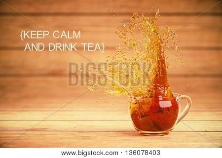 Keep calm and drink tea concept with splashing cup of tea on wooden background. 3D Rendering