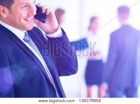 Portrait of young businessman in office with colleagues in the background and using mobile.