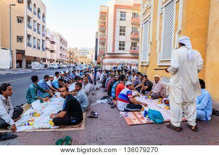 Dubai, June 14, 2016: men are gathered for iftar dinner near a mosque in Bur Dubai, UAE