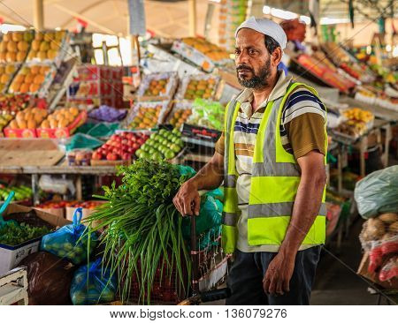 Dubai, June 4, 2016: a delivery worker with a cart full of fresh produce at the fruit and vegetable market in Dubai, UAE