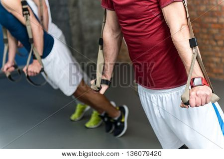 Close up of trained male body. Young men are exercising with trx equipment. Focus on smart watch on his arm