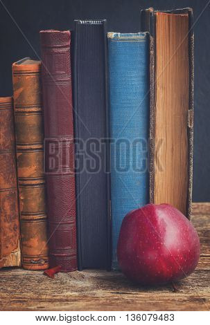 Wooden bookshelf with row of antique books and apple close up, retro toned