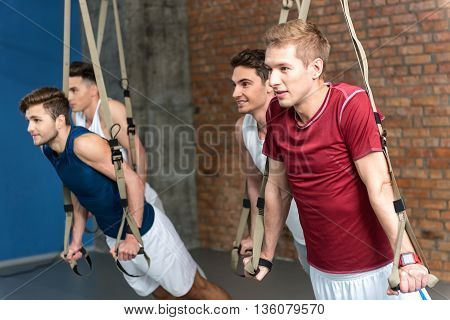 Strong four men are doing push-ups and smiling. They are standing and leaning hands on trx strap