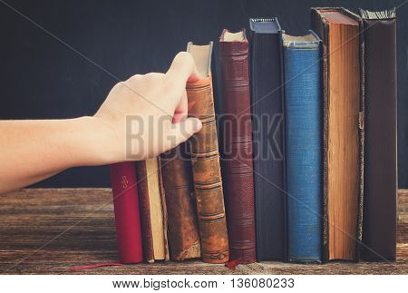 Hand taking book from wooden bookshelf with row of antique books, retro toned