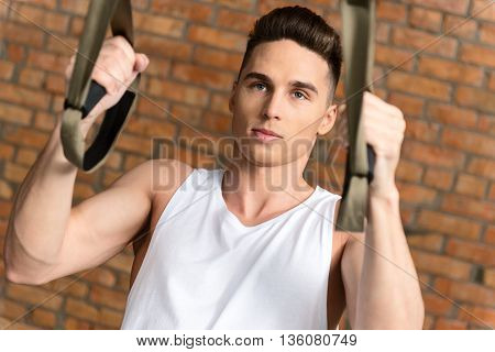 Strong young sportsman is exercising in gym with concentration. He is standing and holding trx bands