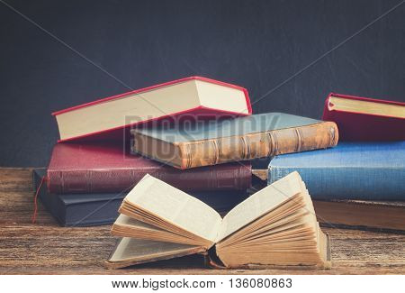 Open old book with pile of closed on wooden bookshelf , retro toned