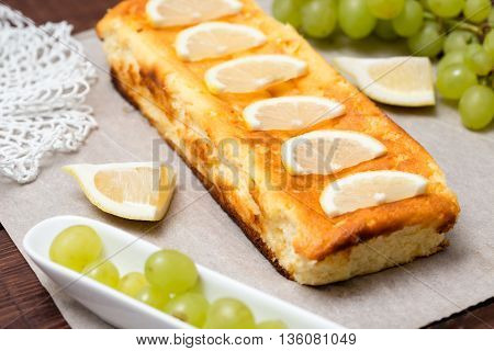 cottage cheese pie is decorated with lemon and grapes.