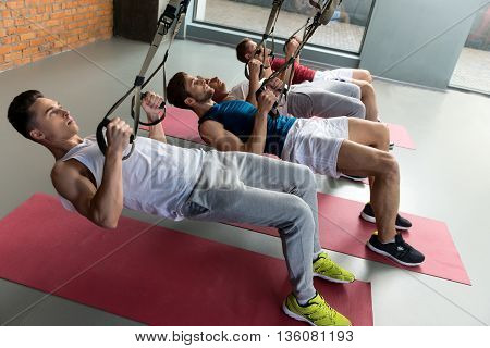 Strong young sportsmen are doing push-ups with efforts. They are holding trx straps