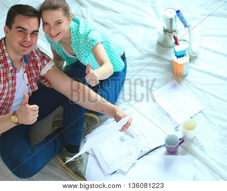 Young couple sitting on floor and calculating about they savings.