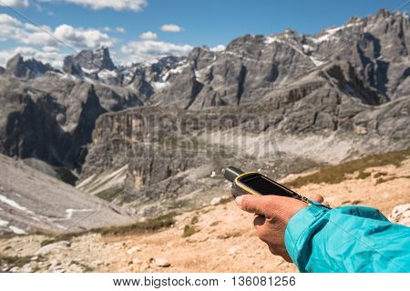 GPS navigator in hand against Dolomite Alps