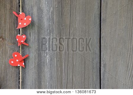 Three red hearts on old wooden background. Country style. Celebratory background.