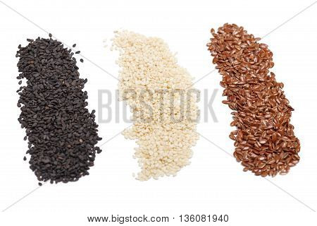 Seeds of white and black sesame and flax on white background. Closeup view selective focus