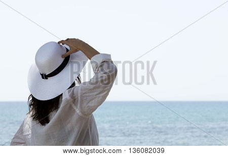 woman looking the horizon with a white straw hat