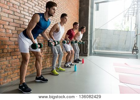 Strong four athletes are lifting dumbbells with efforts. They are standing and looking forward seriously