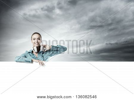 Smiling young woman leaning on big white blank banner