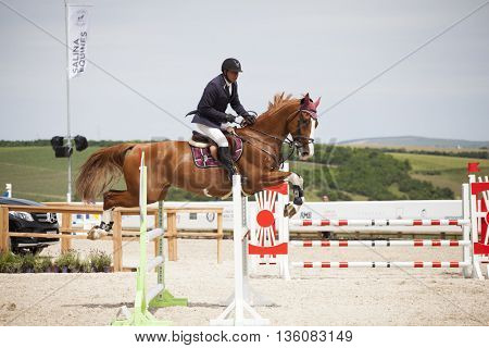Turda, Cluj,, Romania - June 18, 2016: An unidentified competitor jumps with his horse at the Salina Equines Horse Trophy , June 18, 2016 in Turda, Romania