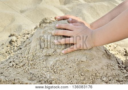 Little Boy Playing On The Beach In The Sand. Child Sculpts Figures Out Of The Sand. Activities In Th