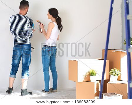 Portrait of happy smiling young couple  painting interior wall of new house.