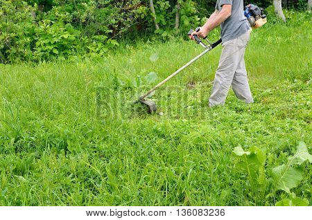 Man mowing lawn mower green young grass. Gardener doing seasonal work. Clearing the garden of weeds.