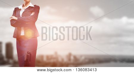 Close up of businesswoman with arms crossed on chest on modern city background