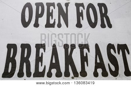 a White wooden open for breakfast sign