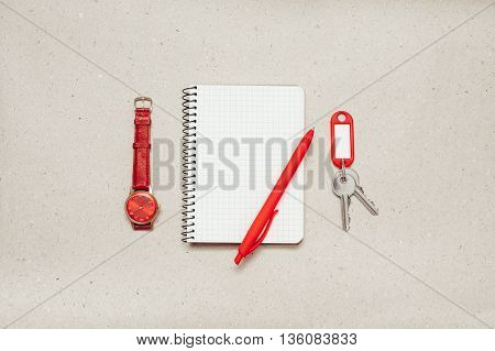Empty notepad with red pen and red wrist watch on paper background, keys with trinket