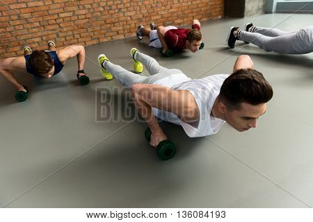 Skillful male athletes doing push-ups with efforts. They are holding weights