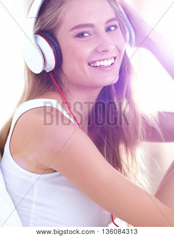 Portrait of beautiful woman in morning listening music sitting on bed at home.