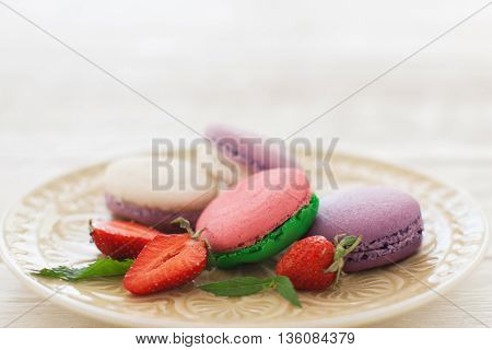 Sweet colorful macaroons with strawberry slices on plate copyspace. Front view on white glass plate with colorful macaroons served with fresh strawberry. Some free space