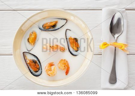 Seafood cream-soup with spoon flat lay. Top view on bowl with seafood cream-soup with shrimps and mussels and spoon on napkin on white wooden background