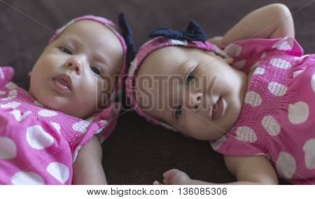 Cute twins babatka with headband with ribbon and pink dress with white polka dots