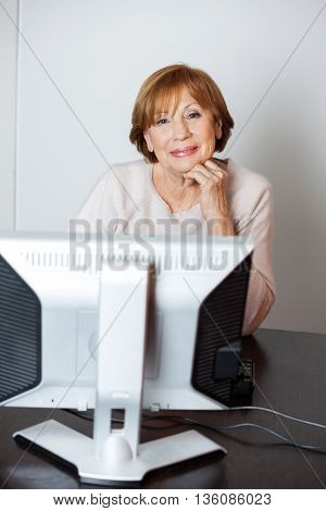 Confident Senior Woman Using Computer In Class